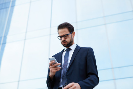 despairing: Despairing businessman reading text message while holding mobile phone