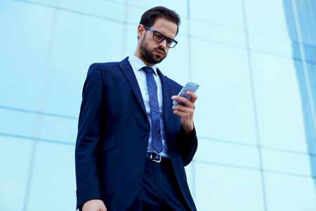 insider information: Unhappy employee read text message on cell phone standing against skyscraper office building