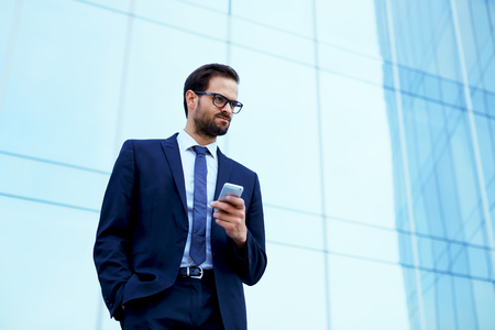moneymaker: Portrait of young executive looking stressed standing near office with smart-phone in the hand Stock Photo