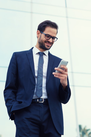 moneymaker: Happy businessman smiling as he reads a text message standing outside the office Stock Photo