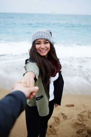 san valentin: First-person portrait of charming girlfriend holding boyfriend hand, young couple in love at romantic walk on the beach
