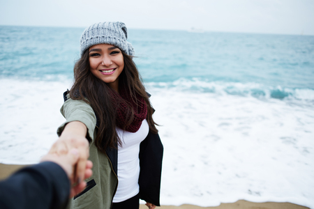 san valentin: Portrait of laughing woman in love with hand held by her boyfriend standing against the ocean