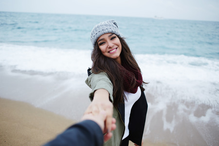 walk in: Portrait of attractive enamored woman walking hand in hand with her boyfriend, romantic couple at walk on the beach during vacation travel
