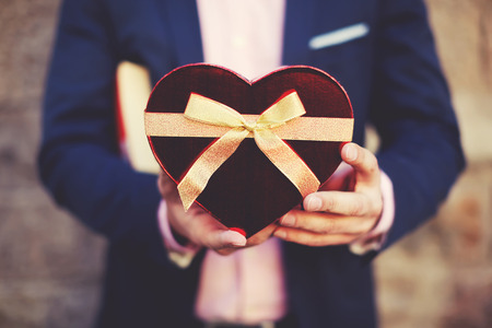 saint valentine's day: Unfocused elegant man holding a red-heart shape gift in the hands on Saint Valentines Day