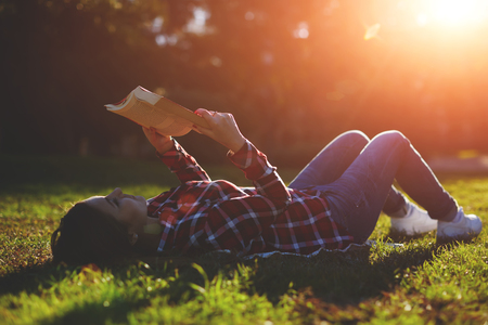 autodidact: A young woman lying on the grass and reading a book, lovely young girl reading a book while lying in a field of grass Stock Photo