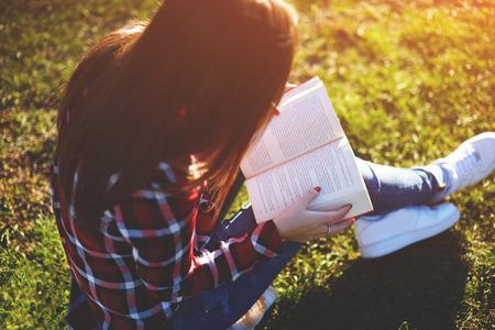 Mujer joven bastante relajada que lee un libro en el césped con el sol que brilla