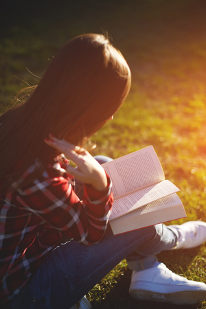 autodidact: A relaxed pretty girl reading an engrossing novel sitting in the park at sunny evening Stock Photo
