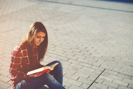 autodidact: Side view portrait of attractive young girl enjoying a good book sitting at sunny evening outdoors
