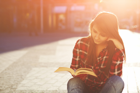 autodidact: Portrait of a young hipster woman enjoying a good book sitting at sunny evening outdoors Stock Photo