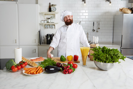 enjoyable: Portrait of enjoyable smiling chef with fresh vegetables on big table standing in the kitchen Stock Photo