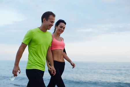 walk in: Sport couple walking along the beach resting after workout, sexy fit woman and man dressed in fluorescent-shirt taking break after run, laughing couple walk along seashore after fitness training Stock Photo