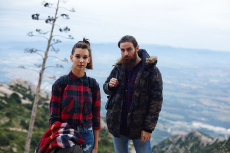 long way: Half length portrait of young hikers resting after long way standing on mountain trail with beautiful view on background
