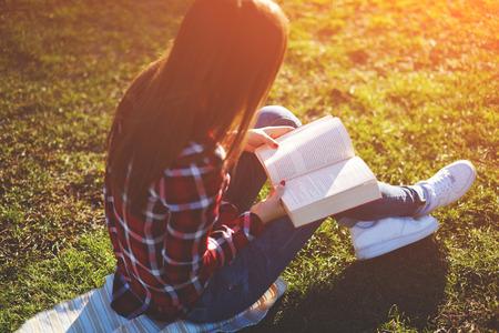 若い素敵な女性リラックス美しい吸収小説を読んでいる公園