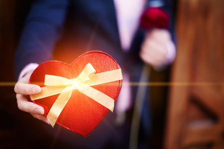 saint valentine's day: Well-dressed man giving a wonderful heart shape gift for lover on Saint Valentines Day Stock Photo
