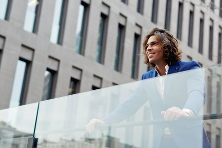 moneymaker: Shot of a happy handsome executive in a suit standing in a city setting Stock Photo