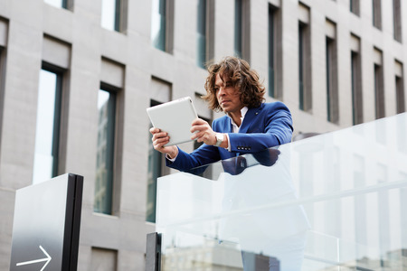 moneymaker: Portrait of a handsome young office worker holding a digital tablet standing outdoors
