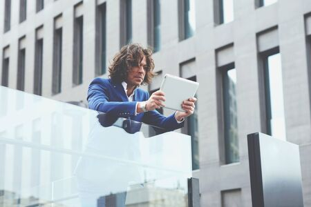moneymaker: Half length portrait of a young well dressed man using a digital tablet standing outdoors Stock Photo