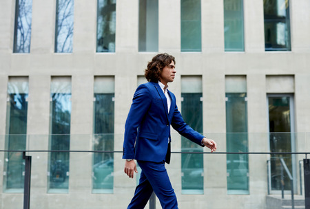 moneymaker: Handsome businessman in a suit walking through the city to work