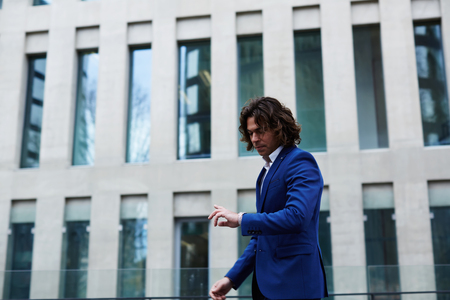 moneymaker: Portrait of a young business man checking time while walking on city street
