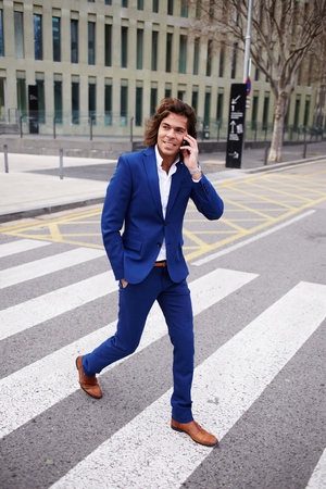 moneymaker: Full length portrait of a young businessman talking on his mobile phone while walking in the street Stock Photo