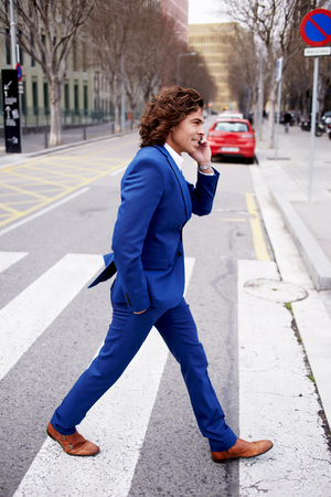 moneymaker: Full length portrait of a young businessman talking on his mobile phone while walking in the street, man in suit walking down a city street having phone conversation