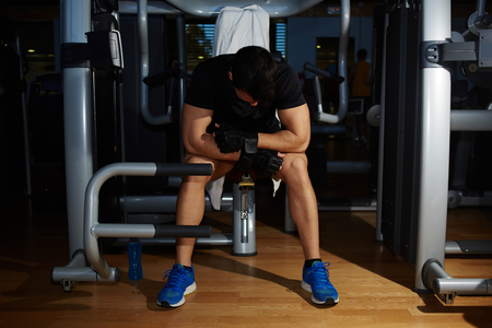 Tired to working out young athlete having a rest sitting on simulator gym equipment, young sportsman lower his head tired to struggle and fight with himself Stock Photo