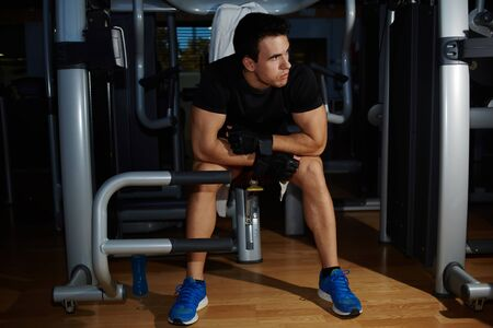 power failure: Full length portrait of young athlete seated on gym equipment and taking a break after workout