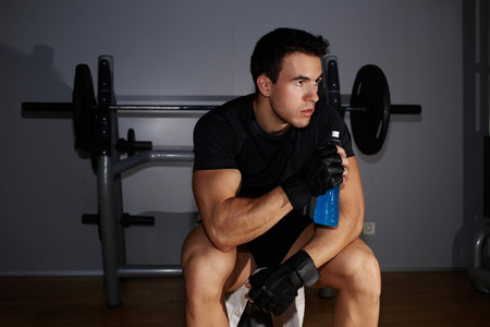 tomando refresco: Half length portrait of professional bodybuilder with weight lifting gloves holding bottle of energy drink and looking away