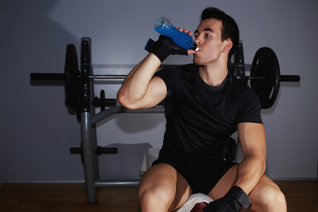 tomando refresco: Athletic man in fitness gloves refreshing with energy drink after hard training Foto de archivo