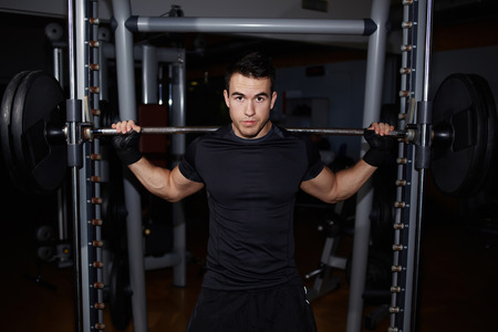 squats: Half length portrait of athletic man doing squats working out with barbell