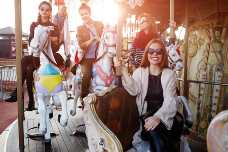 Best girlfriends spending time together riding on a merry go round during their vacation travel holidays, group of attractive women having fun in amusement park Stock Photo