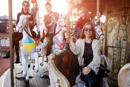 Beste Freundinnen Zeit verbringen zusammen auf einem fröhlich reiten gehen rund während ihres Urlaubs Reisen Urlaub, eine Gruppe von attraktiven Frauen, die Spaß im Vergnügungspark Standard-Bild