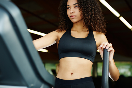 stepping on: Young fit woman dressed in sports bra working out on stepping machine in gym