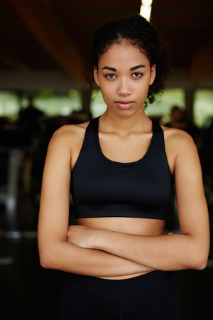 ethic: Portrait of young ethic woman standing with crossed arms relaxing after fitness workout at gym
