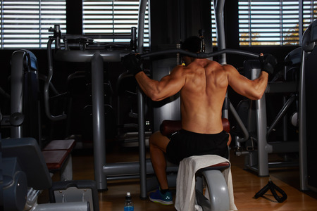 out of body: Young athlete with muscular body working out on pulldown machine at gym