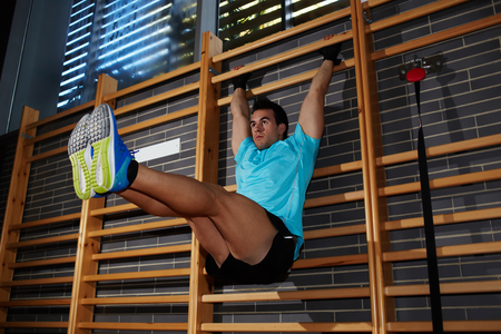 raises: Young athlete with muscular body doing hanging leg raises exercise at gym