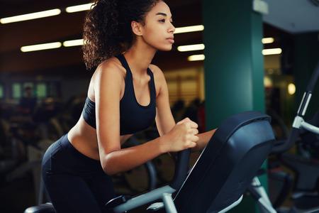 복사본 공간 회전하는 자전거를 타는 체육관에서 매력적인 여자의 측면 샷