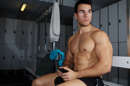 muscular build: Muscular build athlete sitting in gyms locker room having a rest after workout