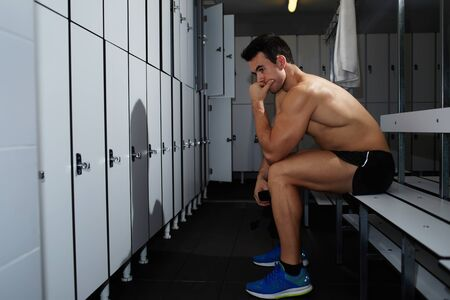 attainment: Attractive muscular build man sitting in gyms locker room after fitness training Stock Photo
