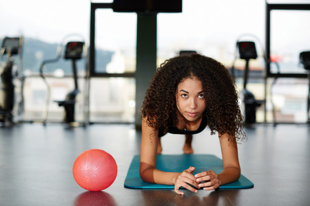 leaning on elbows: Pretty afro american girl leaning on her elbows doing exercise for abdominals at gym