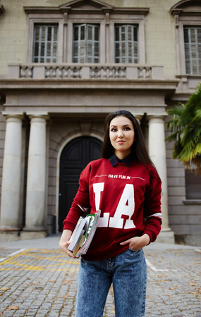 brunnet: Half length portrait of stylish student girl standing with books against university building
