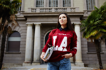 brunnet: Attractive brunette hair student standing on university entrance background holding books