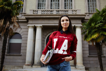 Portrait of asian female student standing against high school building holding some books Stock Photo