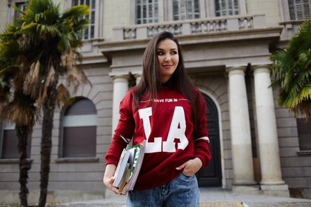 Attractive american student girl standing against university building holding books