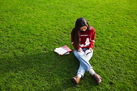 brunnet: Attractive female student sitting with book on the grass while studying during class break Stock Photo