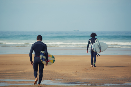 Two professional surfers carrying their surfboards while going to the sea, professional surfers in black diving suits ready to surf walk to the ocean Stock Photo