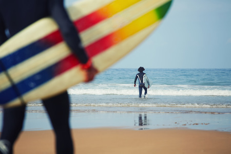 male surfer: Professional surfers carrying their surfboards while going to the sea, professional surfers in black diving suits ready to surf walk to the ocean, close up of surfboard with surfer on background