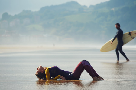 wet suit: Sexy woman lying on wet suit with beautiful professional surfer on background, young surfer looking to the girl while walk to the ocean Stock Photo