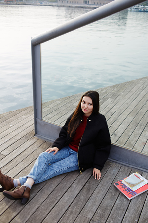 brunnet: Charming tourist girl sitting on wooden pier enjoying beautiful view of Barcelona port
