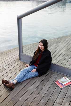 Attractive student girl resting outdoors during her class break in college, female tourist girl enjoying beautiful view sitting on wooden pier near sea